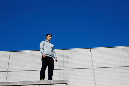 high industrial: Young male tracer standing on the edge of a high industrial urban building while getting ready for jump, brunette free running man on the roof against bright sky background at sunny day Stock Photo