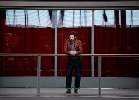 glass fence: Full length portrait of stylish mature man leaning on the glass fence while standing in interior hall against red glass wall background, male clothing designer