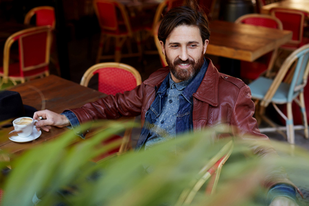 Portrait of handsome aged hipster man sitting in a restaurant terrace enjoying a good day, stylish man looking so satisfied and happy while sitting outdoors
