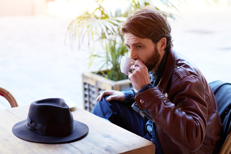 Portrait of handsome fashionable hipster man drinking tea or coffee while sitting on the terrace of beautiful coffee shop, flare sun light 版權商用圖片 - 58206342