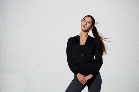area sexy: Portrait of smiling young woman ready for workout standing with dynamic flying hair on white wall background at beautiful sunny day, athletic healthy girl dressed in sportswear posing outdoors Stock Photo