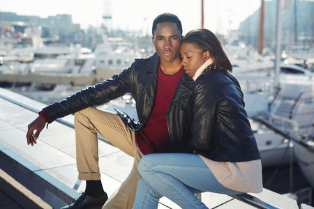 fashionable couple: Portrait of fashionable professional couple of models posing outdoors, embracing black couple enjoying time spending together while sitting in yacht port of Barcelona, vacation holidays