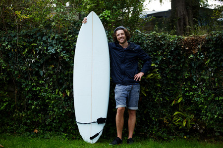 just arrived: Portrait of happy young man with beard holding his surfboard standing on green hedge background at surf camp, just arrived to the surf camp, vacation holidays in nature