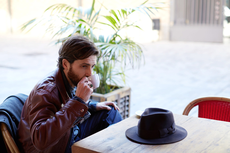 Portrait of handsome fashionable hipster man holding cup of tea or coffee next to his mouth while sitting on the terrace of beautiful coffee shop
