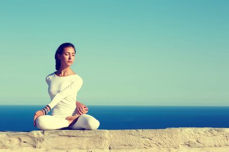 yoga girl: Front portrait of gorgeous young woman practicing yoga on a sunny day with amazing sea horizon on background, woman seeking enlightenment through meditation,relaxed girl performing yoga routine,filter