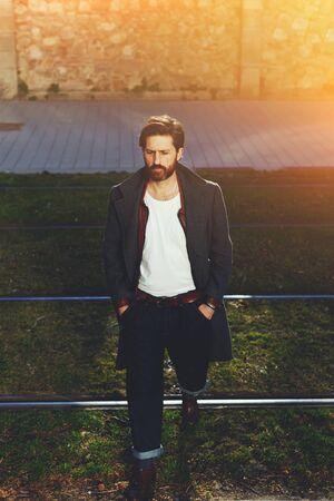 tramline: Portrait of elegant fashionable adult man dressed in coat walking on tramline in urban setting, stylish hipster man walking on the street at sunny evening, flare sunshine