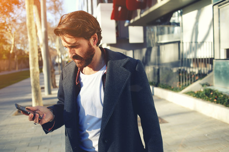 cool guy: Portrait of handsome adult man sending a text message while standing in the city street,business man reading messages,stylish brunette hipster using cell phone at sunny evening outdoors,flare sunshine