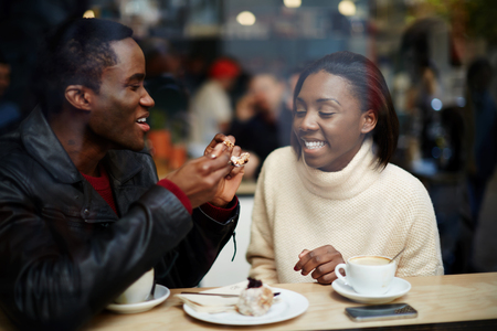 dark skinned: Portrait of young beautiful couple in love having coffee in beautiful cafe, two young people in cafe enjoying the time spending with each other