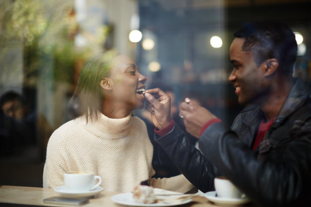 feeding through: Beautiful couple having lunch, view through cafe window, dark skinned handsome man feeding his woman with dessert cake at their dating Stock Photo
