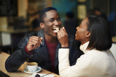 stylish couple: Beautiful dark skinned couple in love having a great time together, man and woman enjoying each other, young woman feeding man with dessert cake at their dating