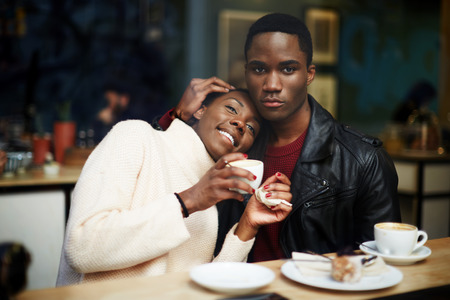 dark skinned: Portrait of young couple in love having fun drinking coffee in cafe, romantic dark skinned couple sitting in coffee shop enjoying the time spending with each other Stock Photo
