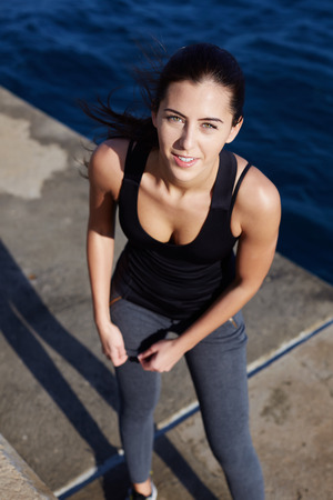 area sexy: Portrait of a beautiful woman getting ready for a workout at the seaside, attractive sports girl having a rest after run outdoors Stock Photo