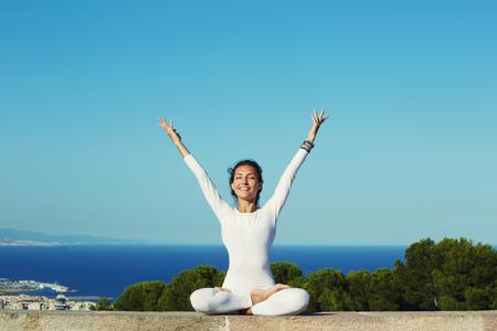 Portret van schitterende glimlachende vrouw het beoefenen van yoga door het verhogen van haar handen voelde zo goed en gelukkig, jonge vrouw op zoek naar verlichting door middel van meditatie, ontspannen meisje uitvoeren van yoga routine, filter