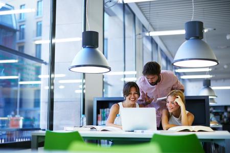 Csoport nemzetközi egyetemi hallgatók szórakozás tanul könyvtár, három munkatársa modern munka co-munkatérben beszél, és mosolyogva, miközben ül az íróasztal asztal, laptop, számítógép
