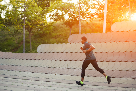 muscular build: Full length portrait of muscular build sports man running along beautiful wall outdoors, male runner working out outside at amazing sunset light, filtered image, flare sunset light Stock Photo