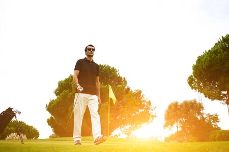 rich life: Full length portrait of professional golf player walking to the next hole on beautiful course, good golf game at sunny summer day on the course, bright flare sunset light