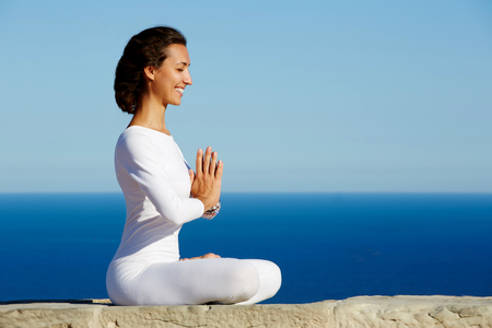 side shot: Side shot of smiling beautiful young woman practicing yoga on a sunny day with amazing sea horizon on background, woman seeking enlightenment through meditation, relaxed girl performing yoga routine