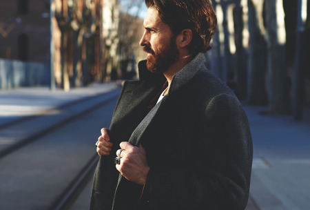 Portrait of fashionable well dressed man with beard posing outdoors looking away, confident and focused mature man in coat standing outside at sunny evening, elegant fashion model
