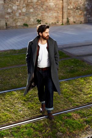 tramline: Portrait of elegant fashionable adult man dressed in coat walking on tramline in urban setting, stylish hipster man walking on the street at sunny evening