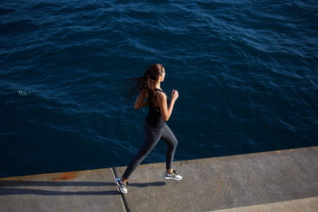 area sexy: Full length portrait of cute young woman out jogging along the coastline at sunny day, dynamic picture with sport girl in action running over ocean waves background
