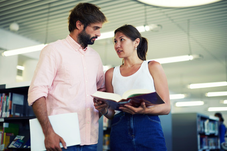 flirtation: Portrait of young couple of students looking at each other while standing in the library, business colleagues having some flirtation while standing in modern work space, classmates in library Stock Photo