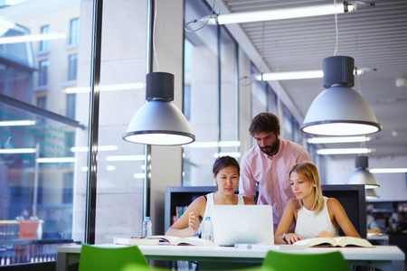 Groep internationale studenten leren in de bibliotheek, drie collega's van het moderne werk co-werkruimte praten en lachen tijdens de vergadering op het bureau met laptop computer, examenvoorbereiding