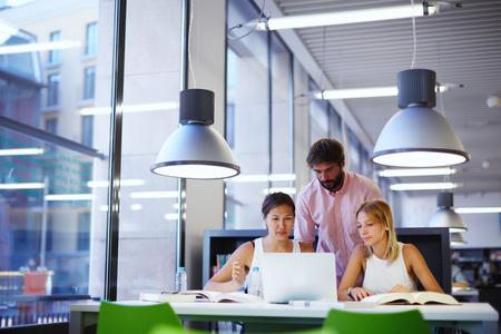 Gruppe internationale Studenten, die in der Bibliothek, drei Kollegen des mitarbeitenden Raumes der modernen Arbeit sprechen und beim Sitzen lächeln, am Schreibtisch mit Laptop-Computer, Prüfungsvorbereitung Standard-Bild