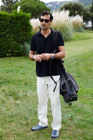rich life: Portrait of adult golf player man standing on beautiful golf course, handsome brunette man in glasses with golf bag on shoulder holding ball in the hands, recreation time with sport Stock Photo