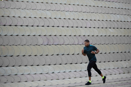 muscular build: Full length portrait of athletic dark-skinned man running along beautiful grey wall outdoors, muscular build young runner working out while jogging in the park