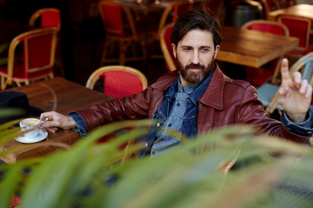 Portrait of handsome hipster man with beard man asking for a bill while sitting in a restaurant terrace Stock Photo