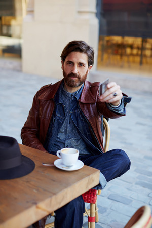 Portrait of handsome hipster man paying for his coffee with a credit card at the cafe, customer paying at a coffee shop with a credit card 版權商用圖片