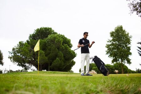 rich life: Full length portrait of handsome mature man playing golf at beautiful summer day on green course, golf player getting ready his club to hit the ball