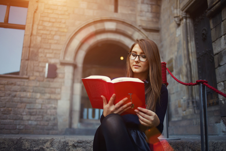 autodidact: Portrait of a female university student reading interesting book on campus, charming teenager sitting outdoors with open book, attractive young girl read absorbing book at beautiful sunny day, flare Stock Photo