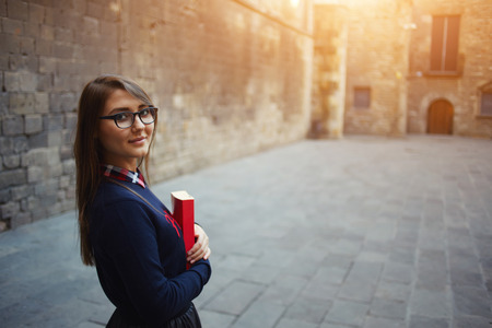 autodidact: Portrait of beautiful young student standing outside holding her book, smiling student girl holding red book close to her chest standing on campus at beautiful day. filtered image, flare light Stock Photo