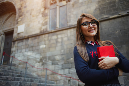 Portrait of a smiling student girl holding her books close to her chest standing on campus, attractive female student in glasses holding red bright book standing outdoors