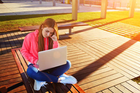 exam preparation: Gorgeous blonde hair female student focused and busy using laptop computer at campus, charming female teenager studying on park bench with open netbook and big copy space for text, exam preparation