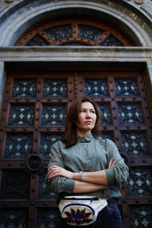 antique asian: Portrait of a stylishly dressed young asian woman standing in front of a wooden antique door, cute hipster girl posing with crossed hands on beautiful background, female fashion designer