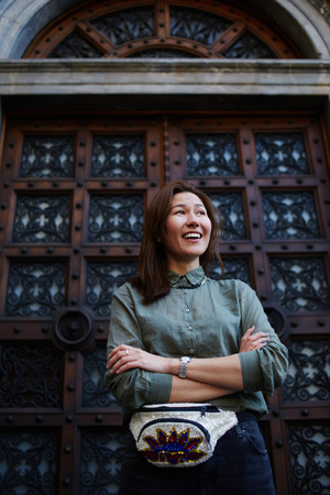 antique asian: Portrait of a stylishly dressed young asian woman standing in front of a wooden antique door smiling, cute hipster girl posing with crossed hands on beautiful background, female fashion designer