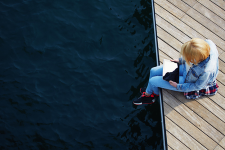 searching information: Top view shot of a young blonde hair woman sitting on a jetty next to a sea while using busy digital tablet with a blank screen, tourist woman searching information on tablet while relaxing on a pier