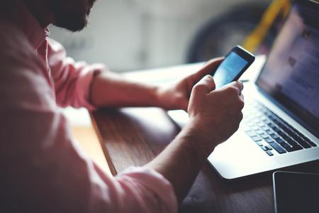 interaccion social: Vista lateral foto de las manos de un hombre que usa el teléfono inteligente en entre vista, parte trasera del hombre de negocios manos ocupadas con teléfono celular en el escritorio de oficina, los mensajes de texto joven estudiante varón en el teléfono sentado en la mesa de madera