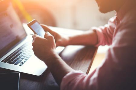 Levágott lövés egy fiatalember otthon dolgozik segítségével okos telefon és notebook számítógép, oldalnézetből egy ember kezében segítségével okos telefon belső, ember az ő coworking helyen használják a technológiát, fellobbanás fény Stock fotó