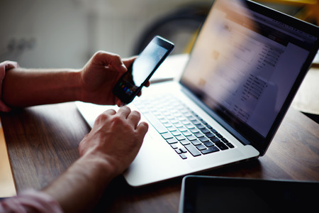 side shot: A cropped side shot of a young man working from home using smart phone and notebook computer, side view of a mans hands using smart phone in interior, man at his coworking place using technology