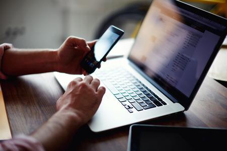 A képen oldalon lövés egy fiatal férfi otthon dolgozik segítségével okos telefon és notebook számítógép, oldalnézetből egy ember kezében segítségével okos telefon belső, ember az ő coworking helyen technológia segítségével