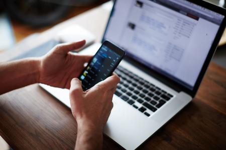 comercio: Cierre de las manos masculinas que sostienen gran teléfono inteligente mientras se conecta a la tecnología inalámbrica, hombre de negocios usando la tecnología moderna se sienta en el escritorio de madera altillo, las personas y los dispositivos modernos de todo el mundo