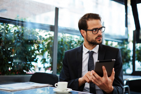 informed: Portrait of smart attractive businessman in glasses drink coffee during his outdoors breakfast, handsome executive holding tablet pc having a coffee on the terrace