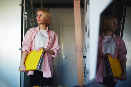 female magazine: Portrait of young stylish woman holding bright yellow book standing near shelf in home interior, creative female designer with big magazine catalog standing in her studio while focused looking away
