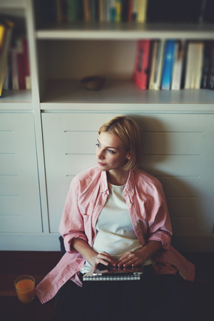 bookshelf digital: Portrait of gorgeous young woman sitting at home bookshelf with her digital tablet while she works with comfort from home, creative pregnant woman sitting on the floor peacefully looking away, filter Stock Photo