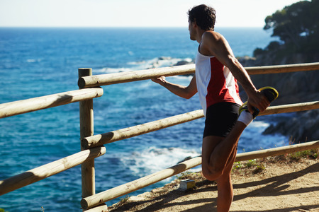 estiramiento: foto de cuerpo entero de un hombre maduro que estira sus músculos isquiotibiales antes de una carrera al aire libre en un día soleado, hombre atlético disfrutar de la vista mientras se hace ejercicio del estiramiento antes de correr