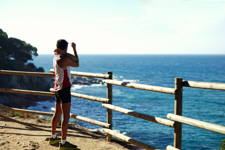 side shot: Side shot of handsome young runner stretching before starting his run while standing on edge of a cliff with a wooden fence and enjoying ocean view from altitude, cross process, filtered image