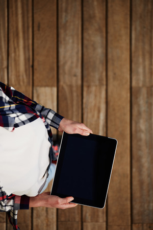 Top view shot of a woman holding digital tablet with a blank screen- closeup, fem a hands holding blank digital tablet against beautiful wooden copy space area, filtered image